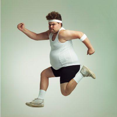 Sportlicher Mann mit Übergewicht zeigt, dass die ausgewogene Ernährung schwer einzuhalten ist