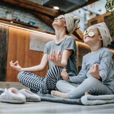 Mutter und Tochter meditieren in Pyjamas mit Gurken auf den Augen und feiern ihre Gesundheit beim Intervallfasten
