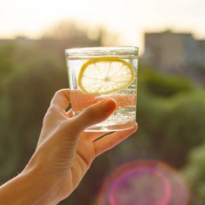 Glas Mineralwasser mit Scheibe Zitrone zum Auffüllen des Flüssigkeitshaushaltes und des Elektrolythaushaltes