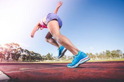 Keto Mythen: Sportliche Leistung. Frau läuft in Sportkleidung über Sportplatz