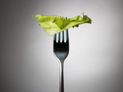 Nicht ausreichend Fett führt zu Hunger bei Keto, einzelnes Salatblatt auf einer Gabel