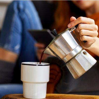 Die Stoffwechselauswirkung von Kaffee beim Intervallfasten, junge Frau giesst Kaffee aus Perkolator in Tasse ein