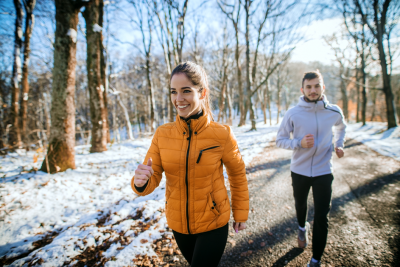 Junge Frau joggt mit Mann im Schnee, stärkt Immunsystem